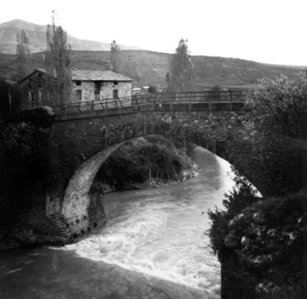Vista del pont d'Orrit, una casa i el seu entorn, Tremp (Pallars Jussà) 1977. Autor: Joan Tous i Casals. Generalitat de Catalunya, Departament de Cultura (http://invarquit.cultura.gencat.cat/).